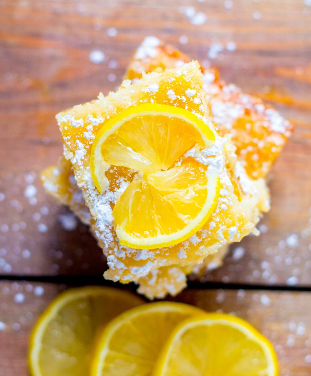 Lemon slices and cake pieces are placed on top of a wooden surface.