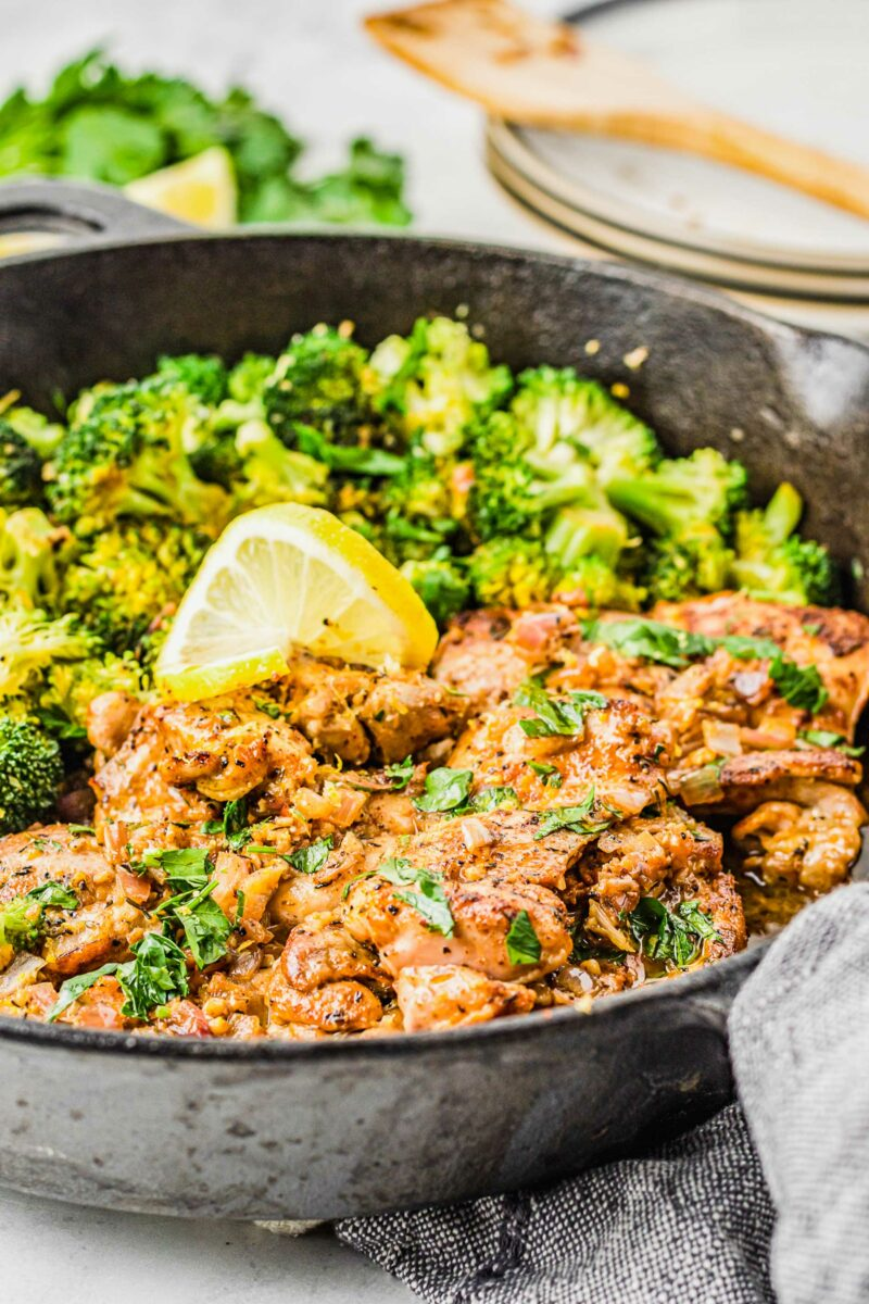 Lemon garlic chicken thighs in a skillet are garnished with fresh parsley.