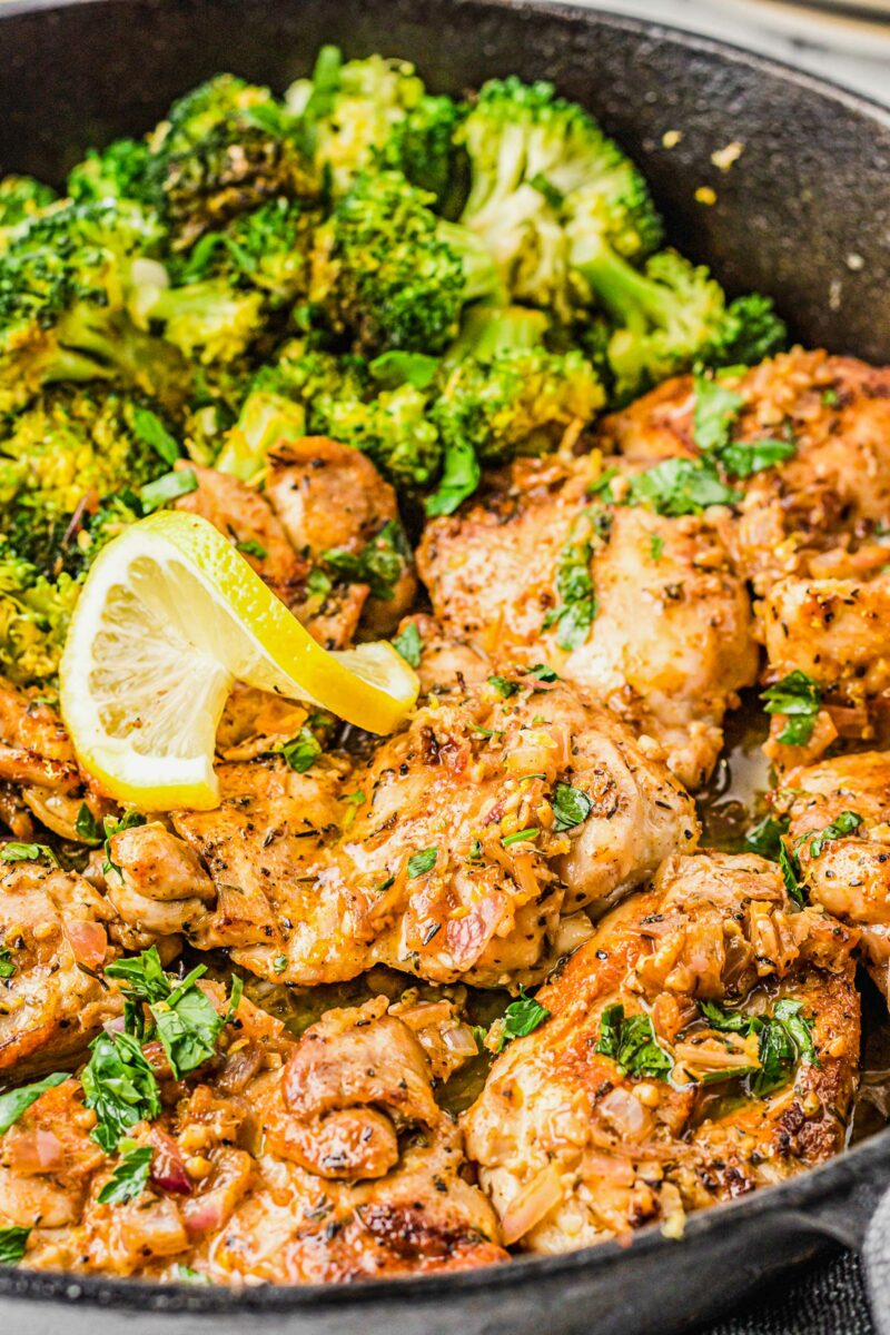 Fully cooked lemon garlic chicken thighs are in a skillet next to cooked broccoli.