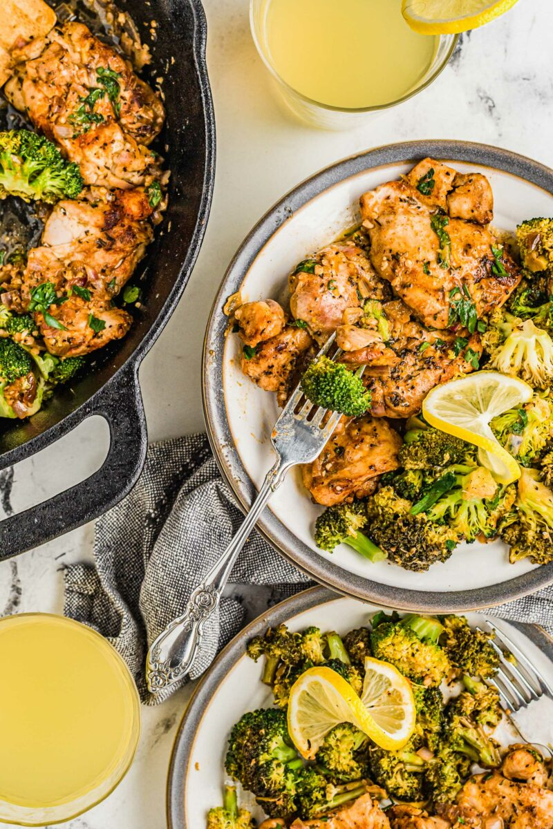 Two white plated with servings of lemon garlic chicken and broccoli are placed next to a skillet.