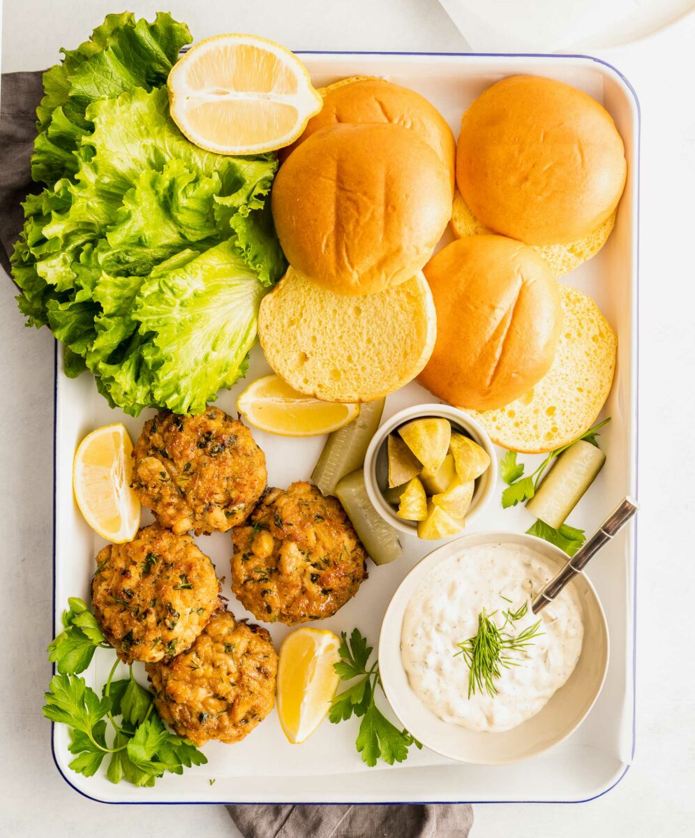 Crab cakes, buns, lettuce and sauce are on a white serving platter.