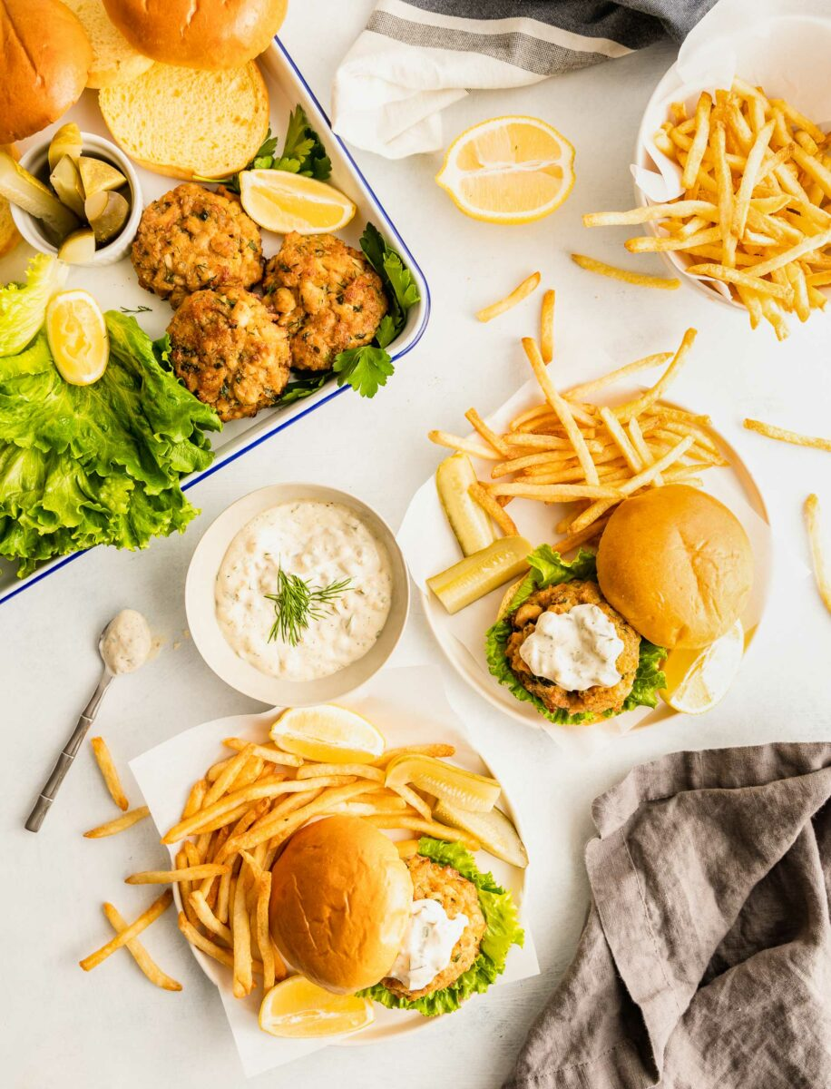 Two plates contain crab cake sandwiches and French fries.