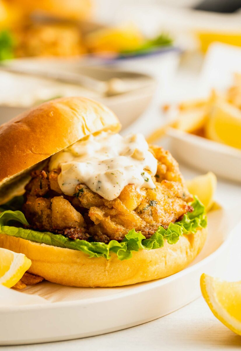 Tartar sauce and lettuce are pictured in a crab cake sandwich.