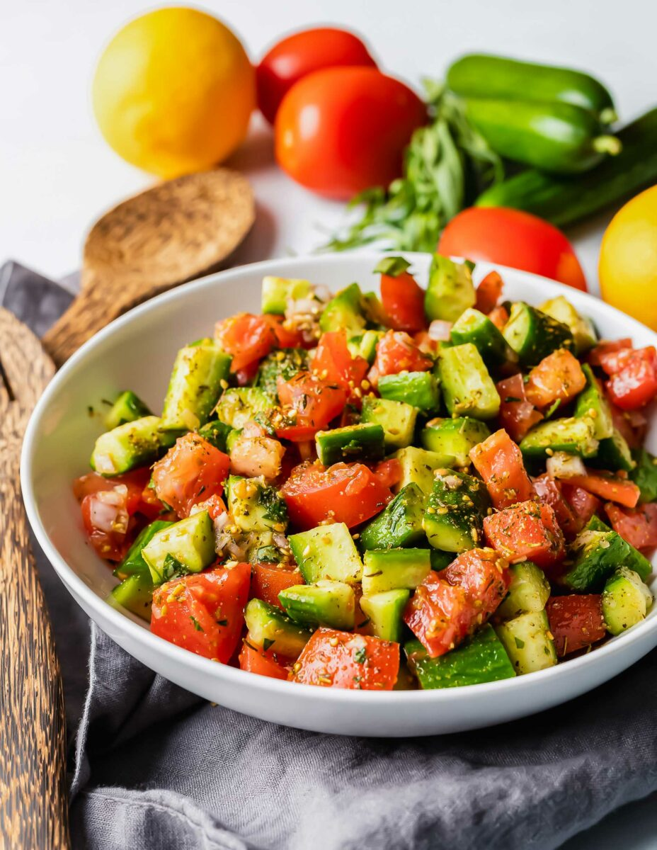 A tomato and cucumber salad has been tossed with wooden salad tossers next to uncut vegetables.