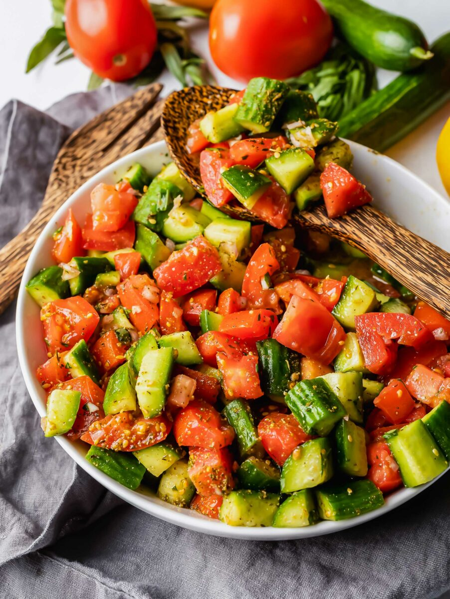 A large wooden spoon is lifting a small serving of tomatoes and cucumbers from the bowl.