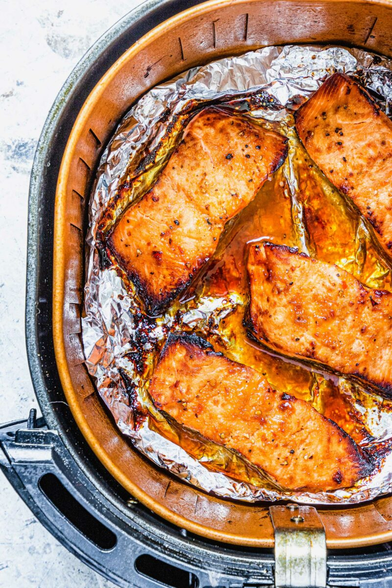 Four salmon fillets are in the basket of an air fryer.