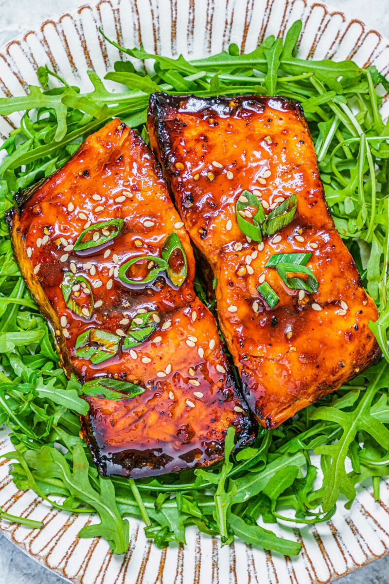 Salmon is topped with sesame seeds and green onions.