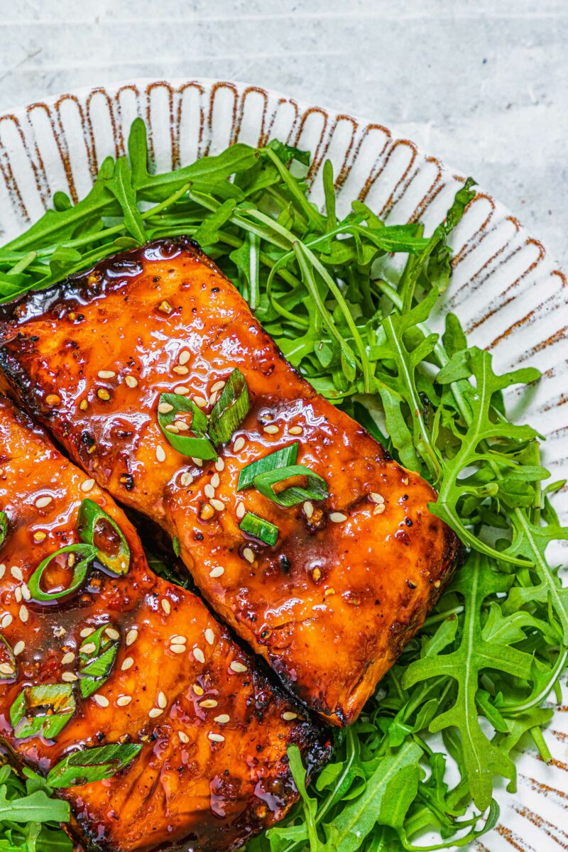 Fresh greens and salmon are on a white plate.