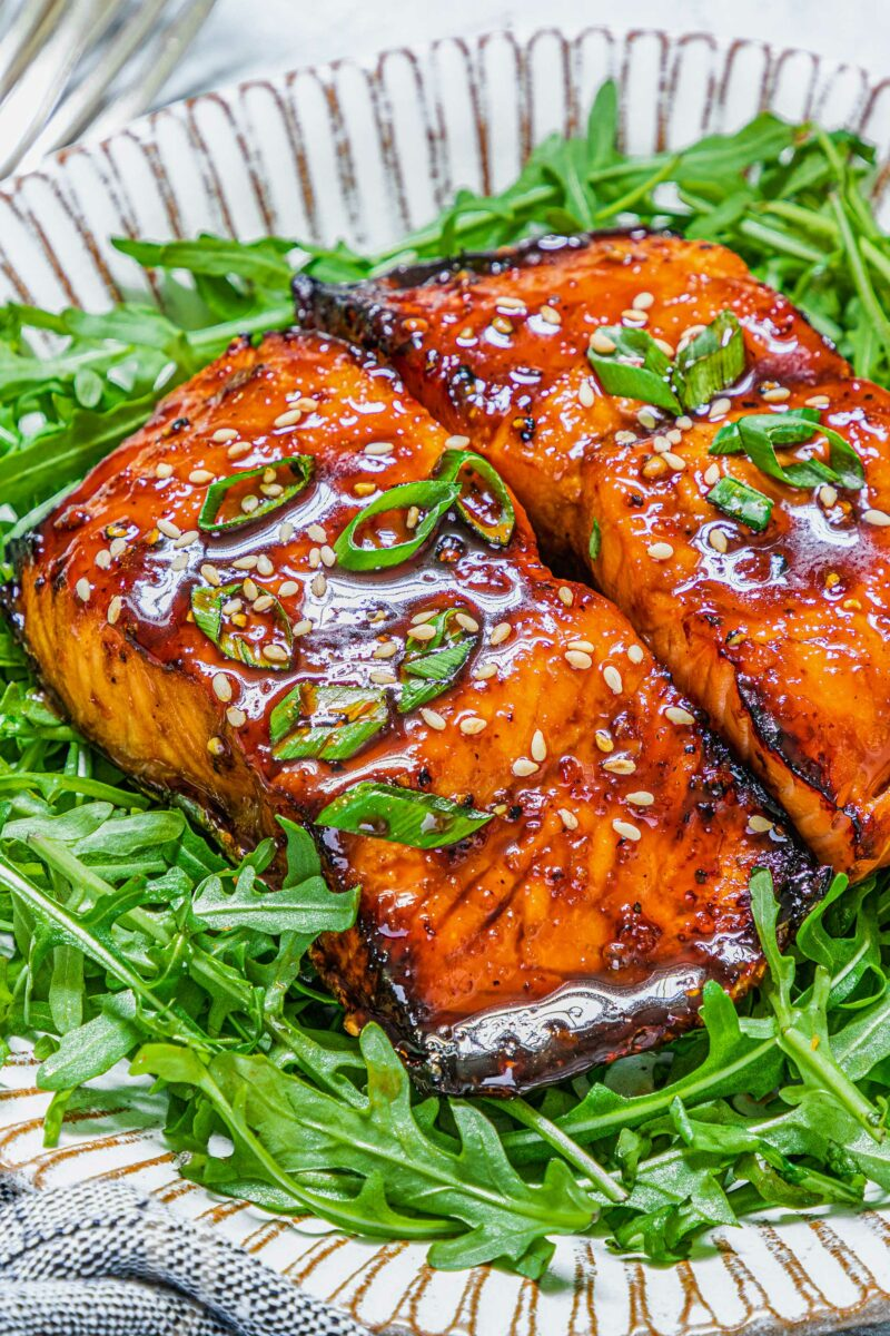 Two pieces of salmon are placed on a bed of fresh arugula.