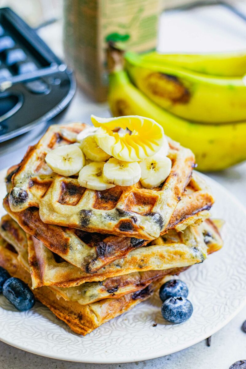 Sliced bananas and whole blueberries garnish a stack of fresh waffles.