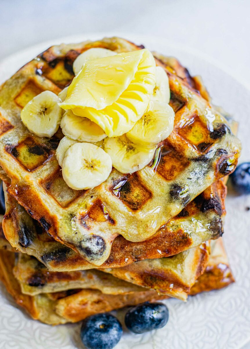 Freshly cooked waffles are stacked and drizzled with honey on a white plate.