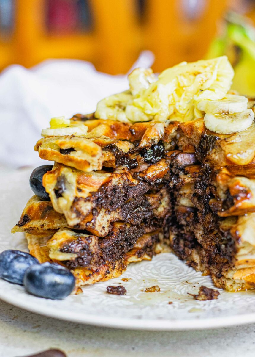A big stack of waffles bas been cut through to reveal a chocolatey center.