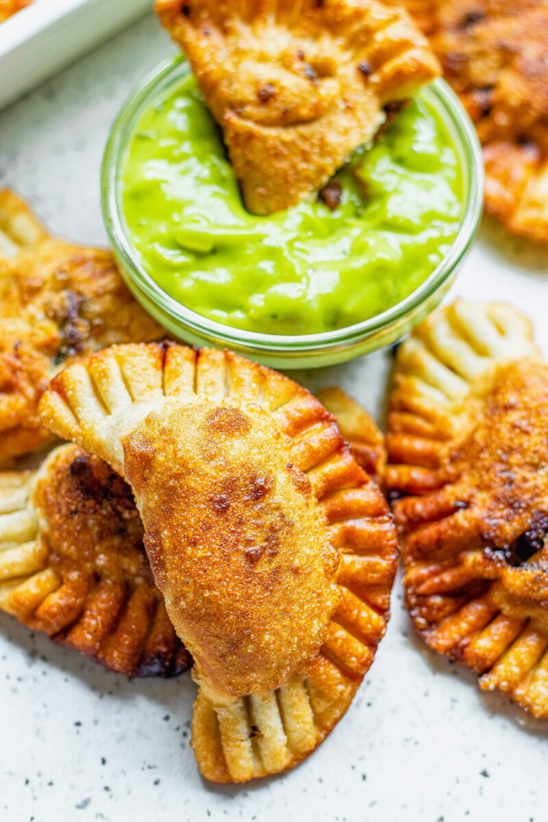 An empanada is being dipped into green sauce.