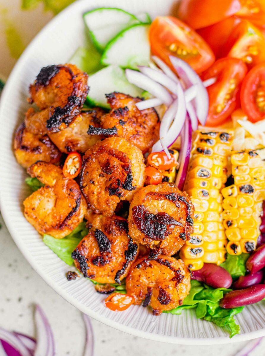 A large portion of blackened shrimp bowl is ready to be eaten.