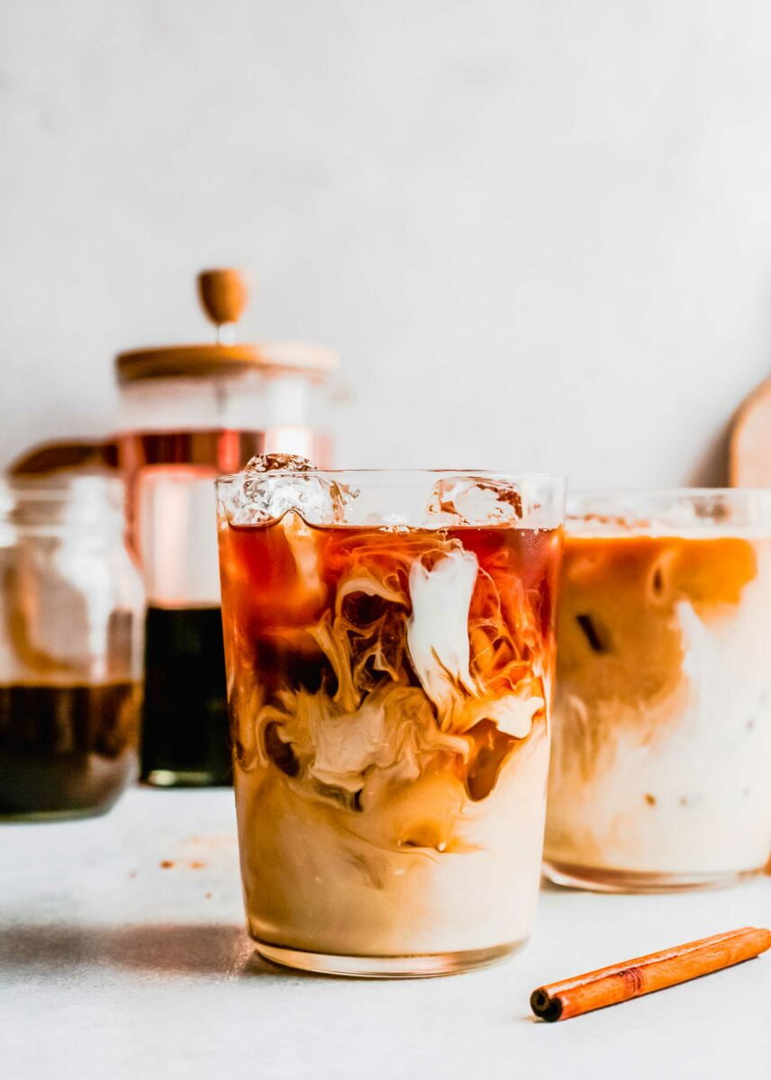 A small glass is filled with oat milk, ice, and espresso.