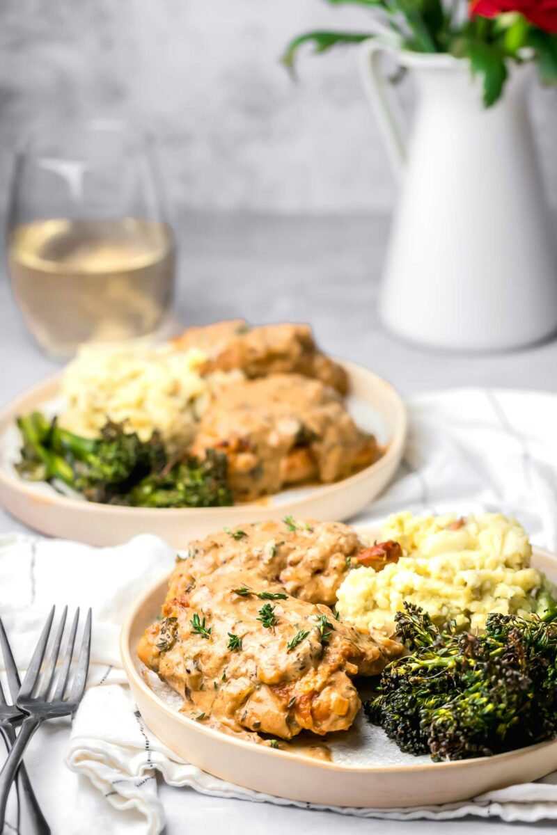 A plate with chicken thighs, broccolini and mashed potatoes is placed on a white tea cloth.