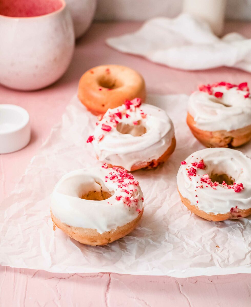 Four donuts are glazed and garnished with raspberries, while one is plain.