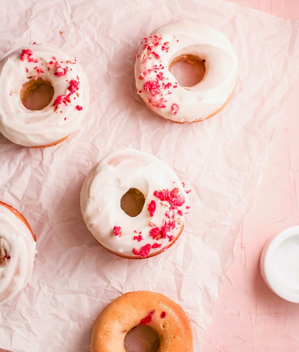 Donuts are garnished in white icing and freeze dried raspberries on a sheet of parchment paper.