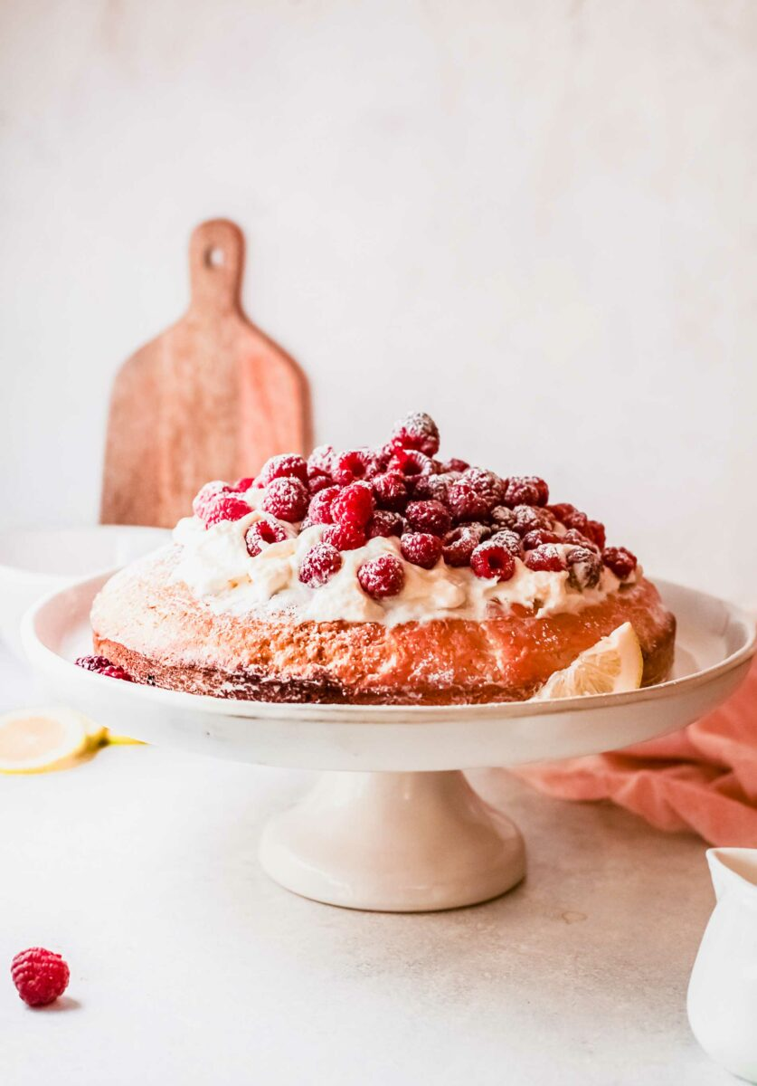 A raspberry olive oil cake is on a white cake stand.