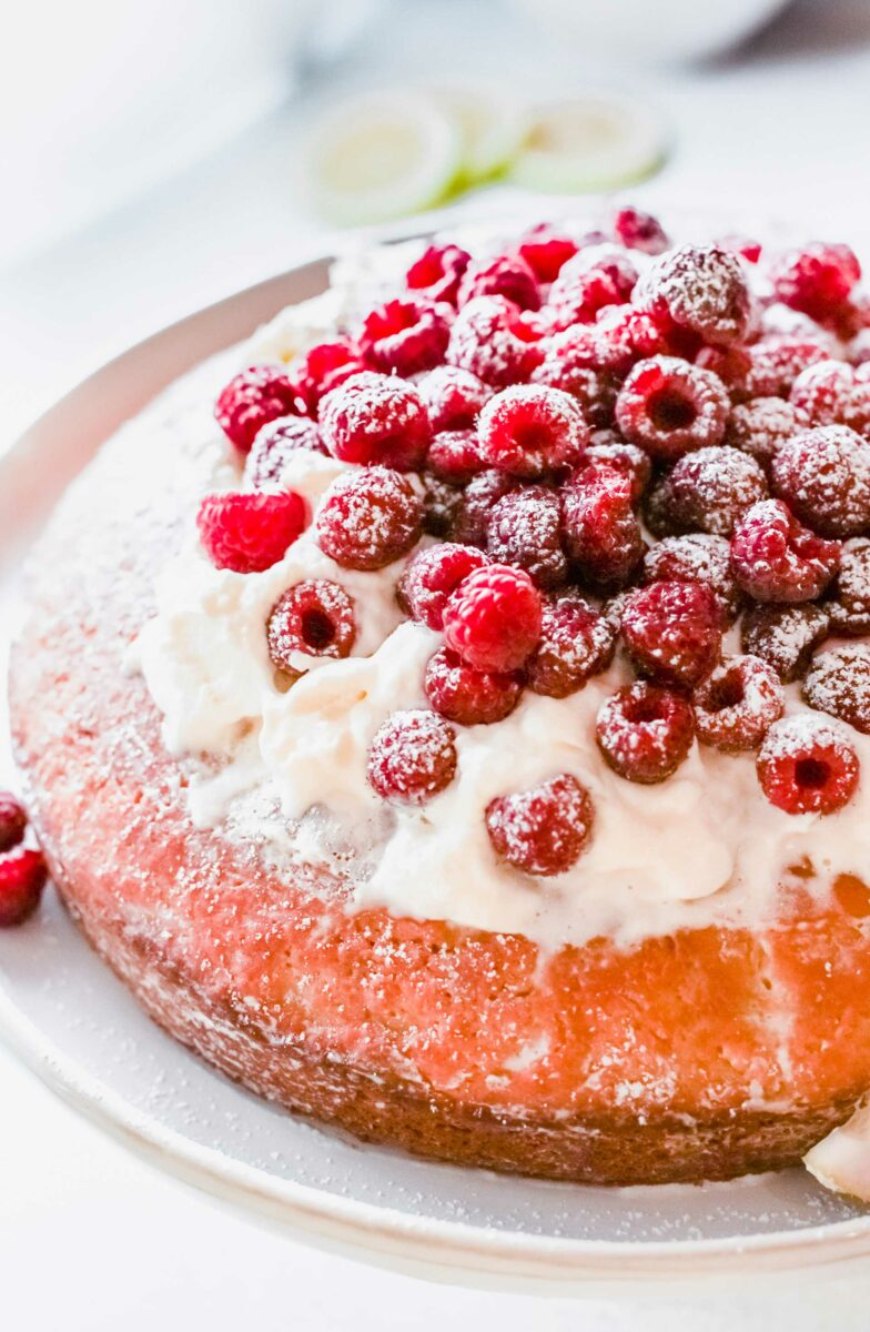 Pink raspberry cake is topped with whipped cream and berries.