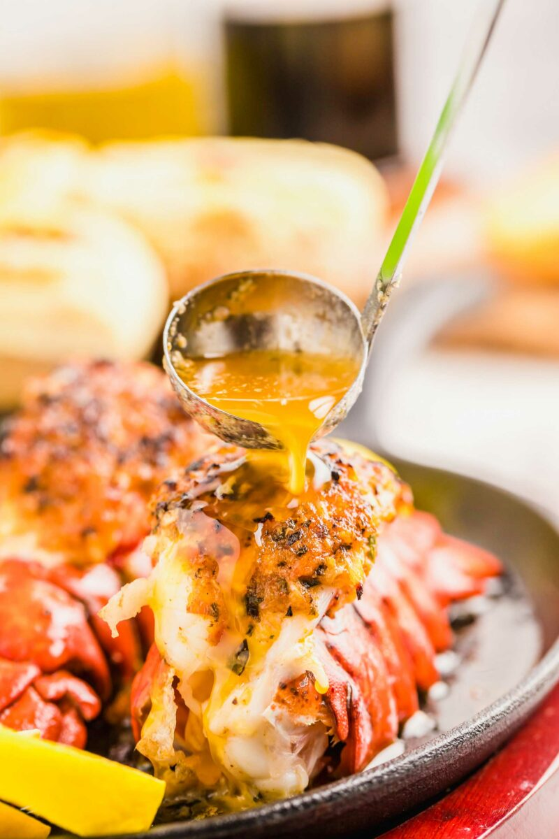 Butter is being poured atop a cooked lobster tail.