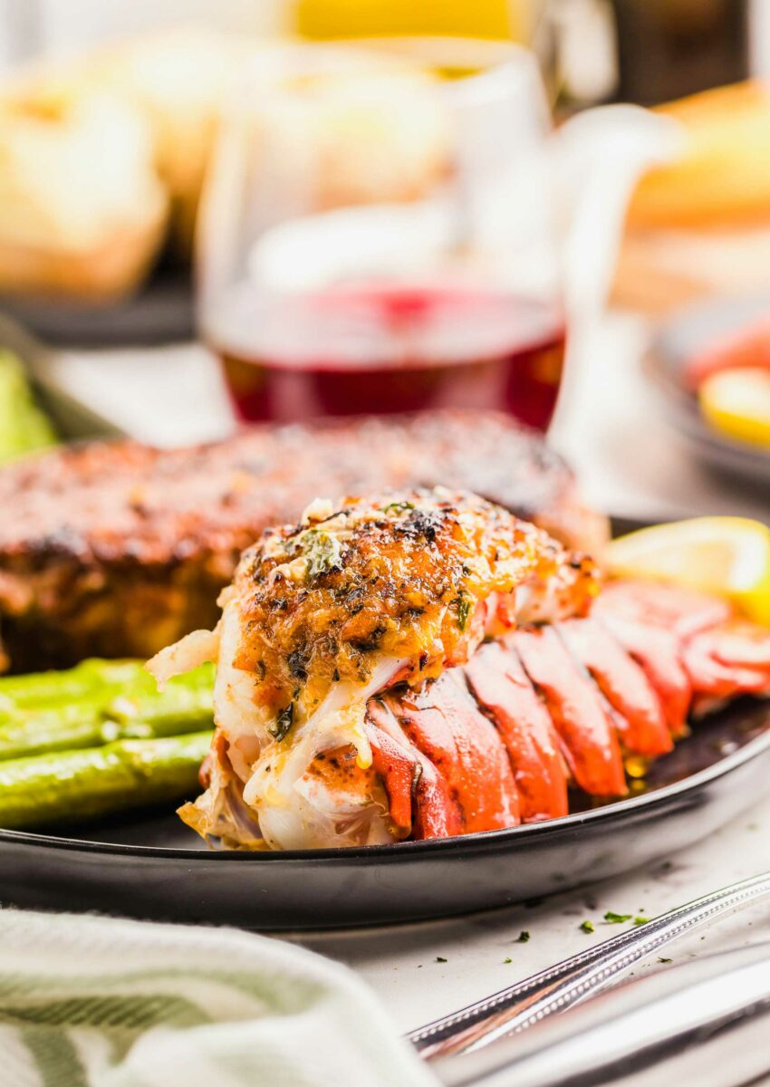 A lobster tail is fully cooked on a black plate.