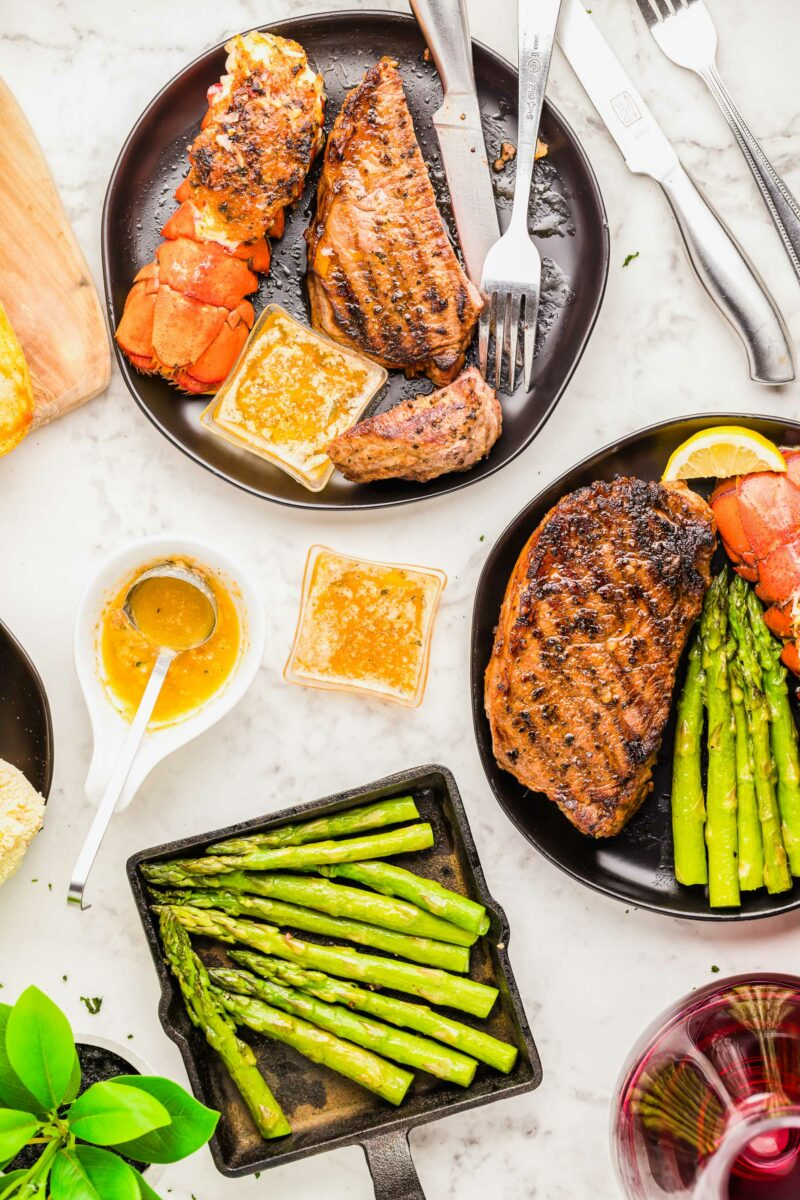 Asparagus is plated next to two plates of surf and turf.
