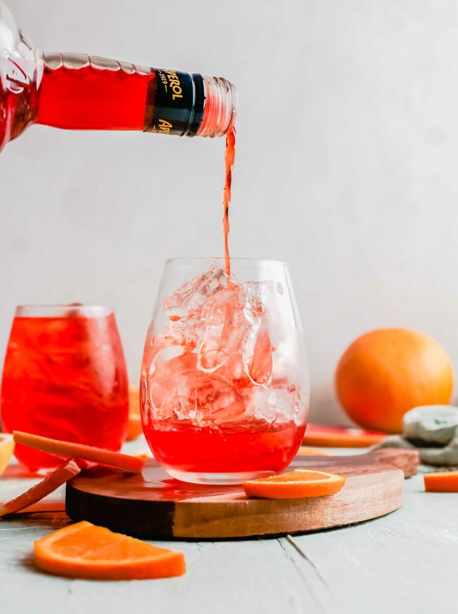 Aperol is being poured into a wine glass.