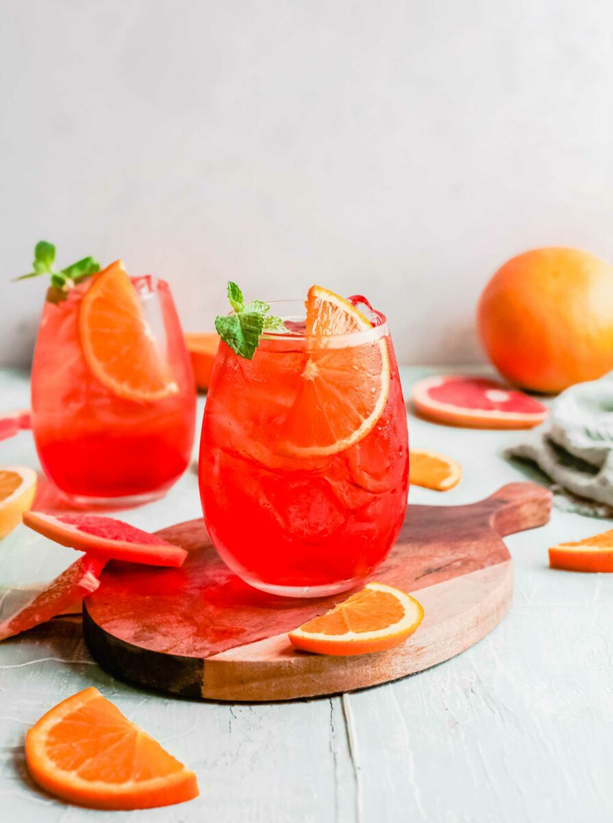 Two aperol spitzes are placed next to several orange slices.
