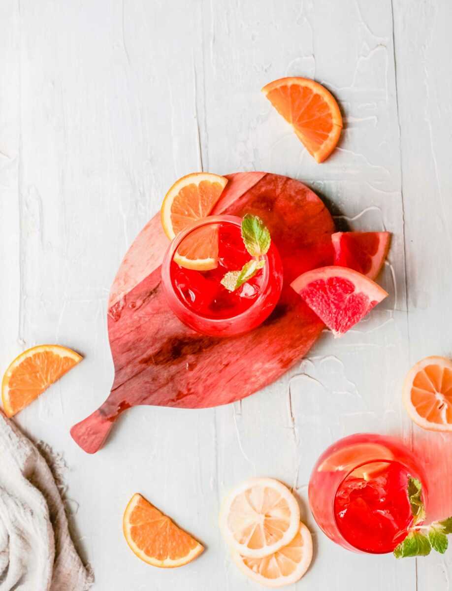 An aperol spritz is placed on a round wooden cutting board.