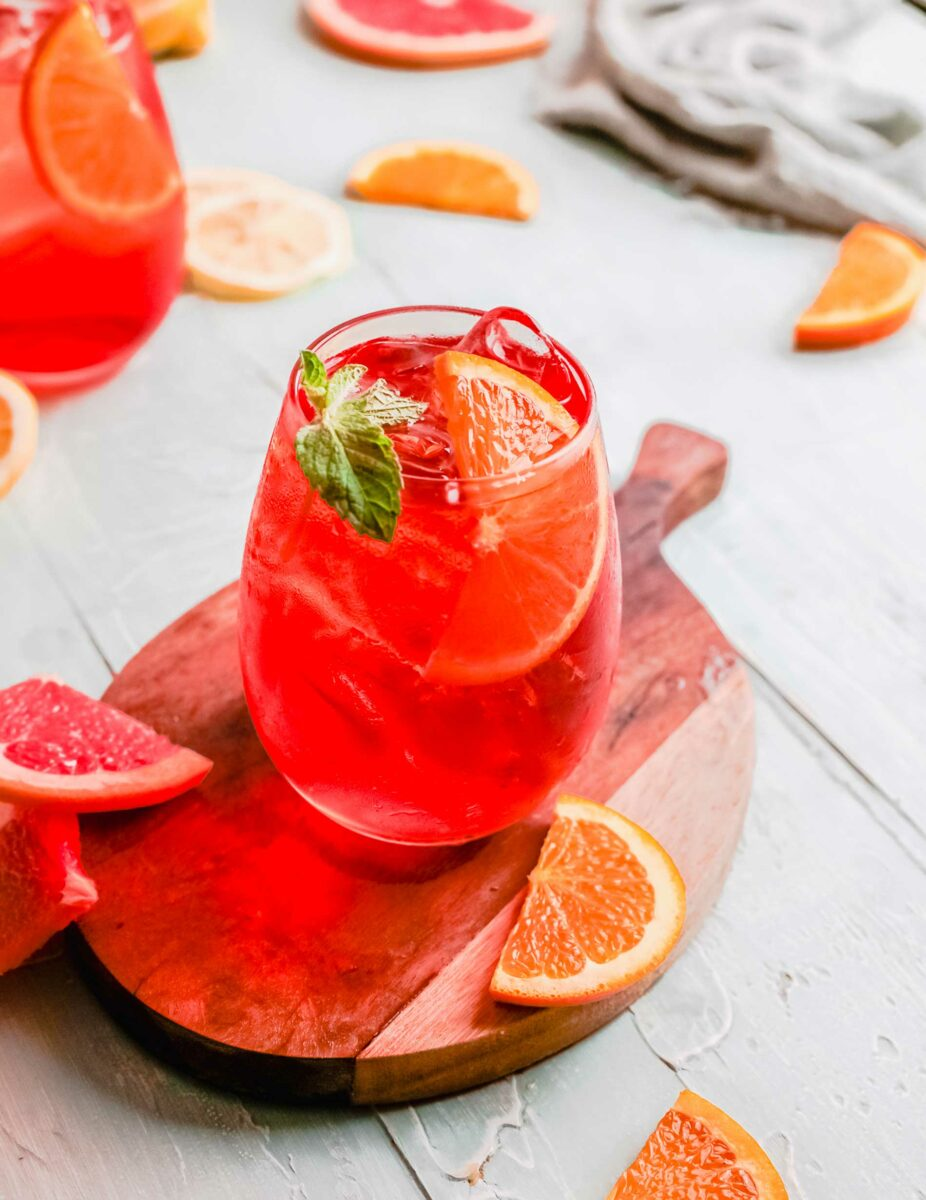 An aperol spritz is garnished with a mint leaf and an orange slice.