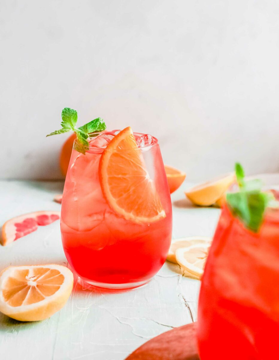A wine glass is filled with aperol spritz, ice, and an orange slice.