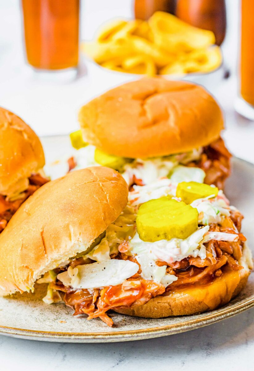 The top bun of a sandwich is put to the side to reveal pickles, coleslaw and pulled chicken.