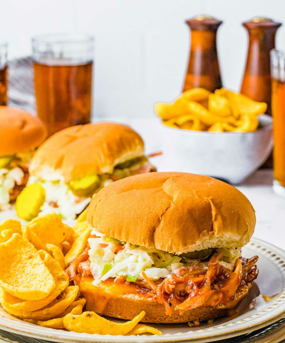 A BBQ chicken sandwich is on a plate next to some chips.