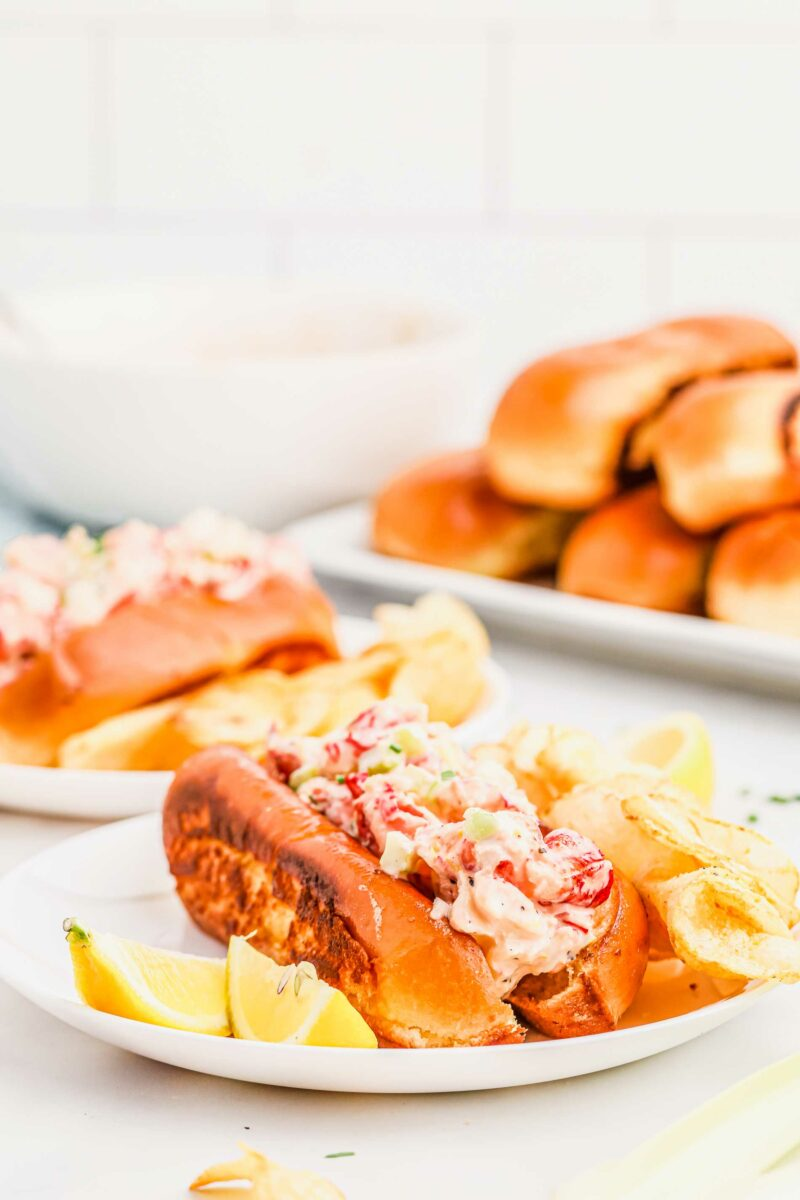 Lemon wedges, a lobster roll, and chips are on a white plate.