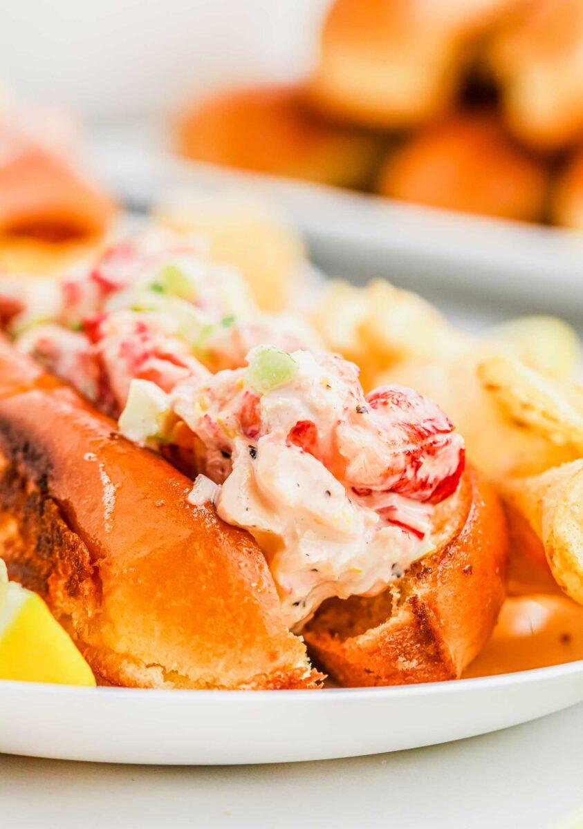 Lobster and mayonnaise mixture fill a brioche hot dog bun.