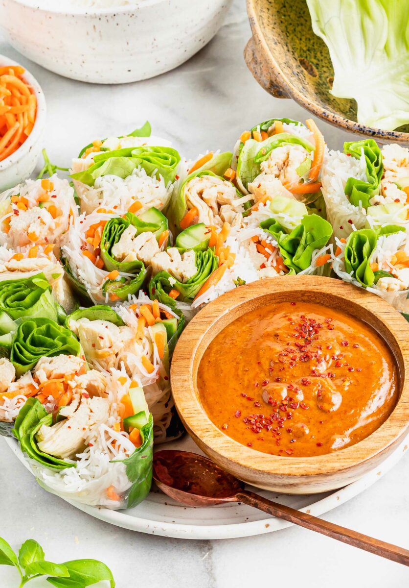 A bowl of satay sauce is placed next to chicken summer rolls.