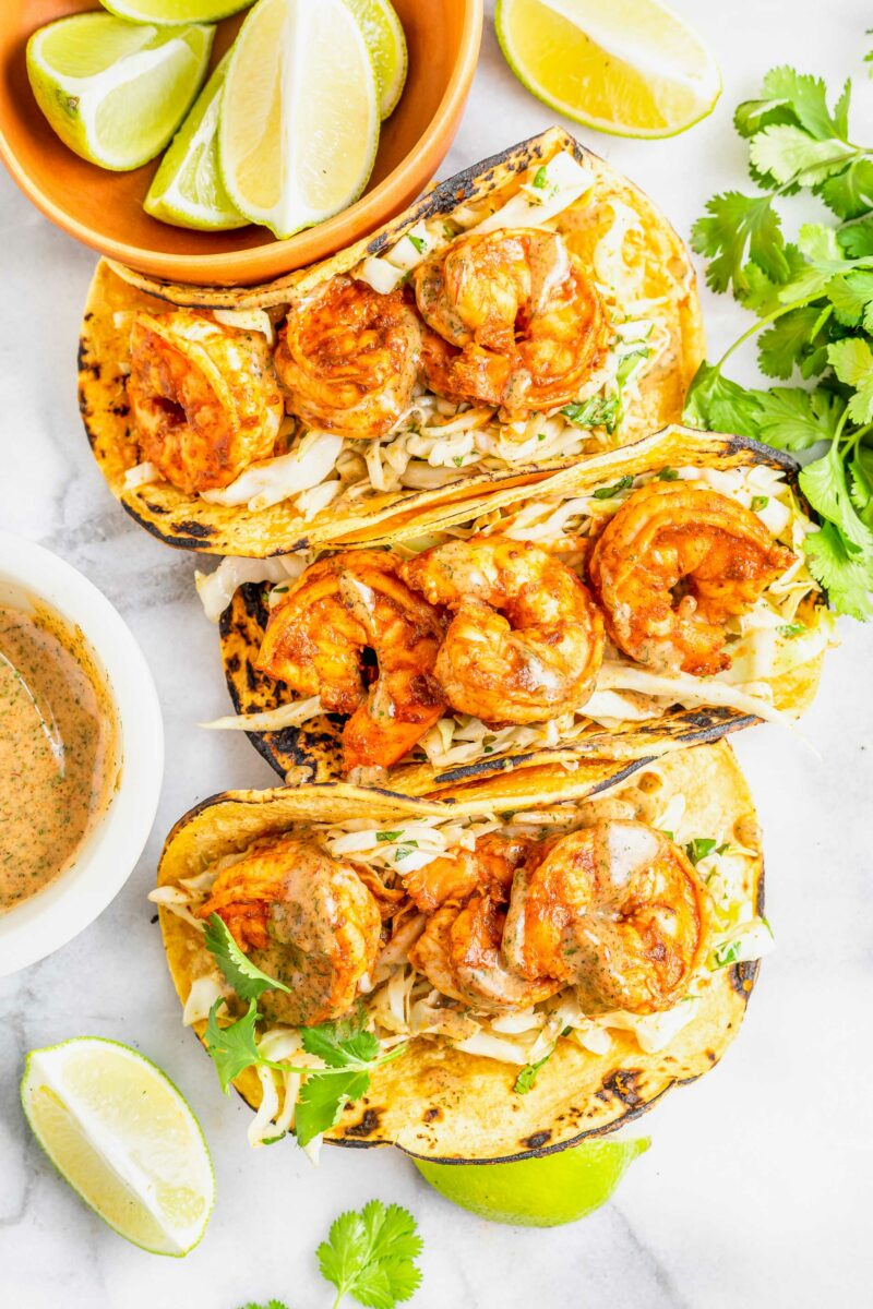 Three shrimp tacos are placed on a white surface.