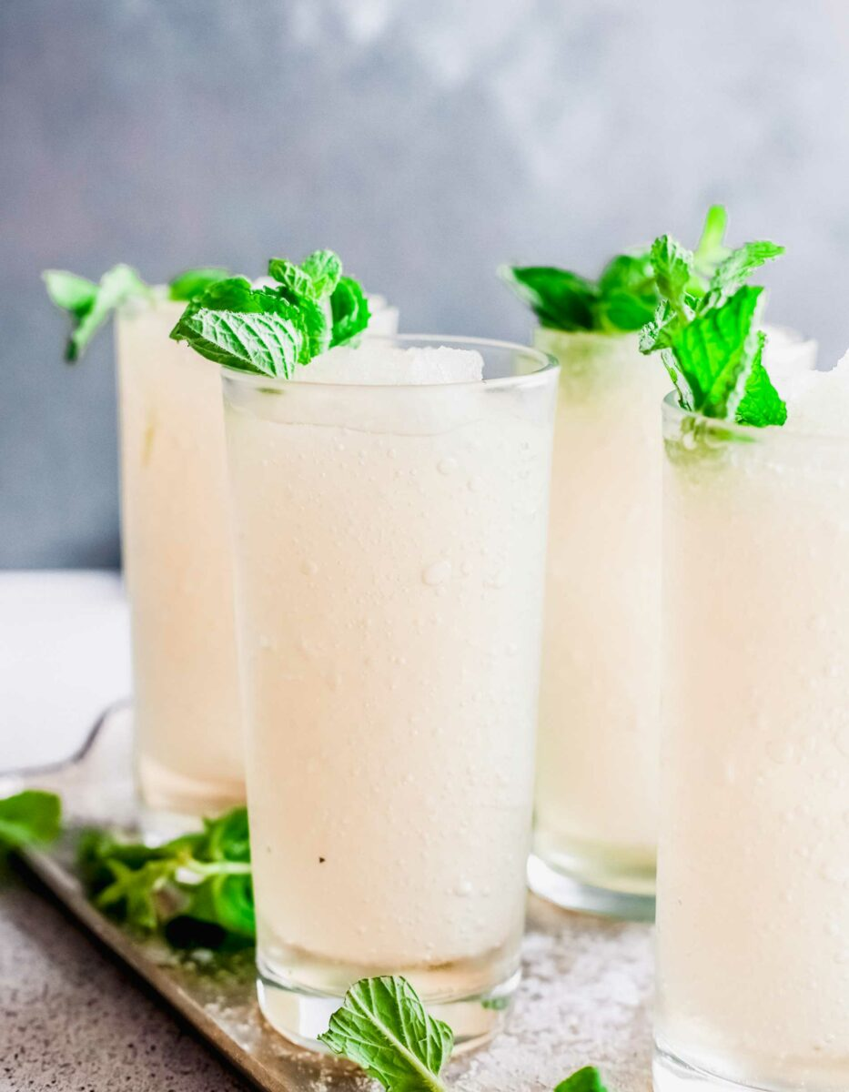 Four frozen mint juleps are placed on a serving tray.