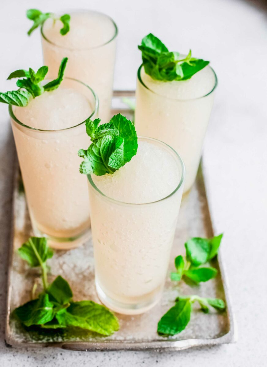 Mint sprigs sit on top of frozen cocktails.