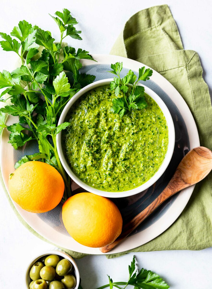 Herbs and lemons are placed next to a white bowl filled with gremolata.