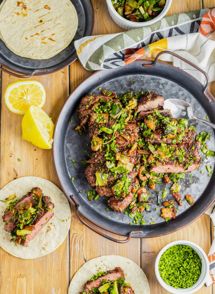 Squeezed lemons and filled corn tortillas are placed next to a large portion of steak and herb topping.