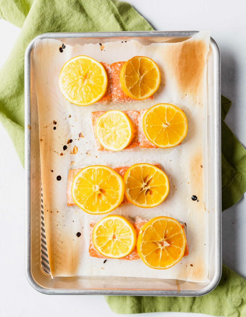 Four salmon fillets are on a prepared baking sheet, each garnished with two lemon slices.