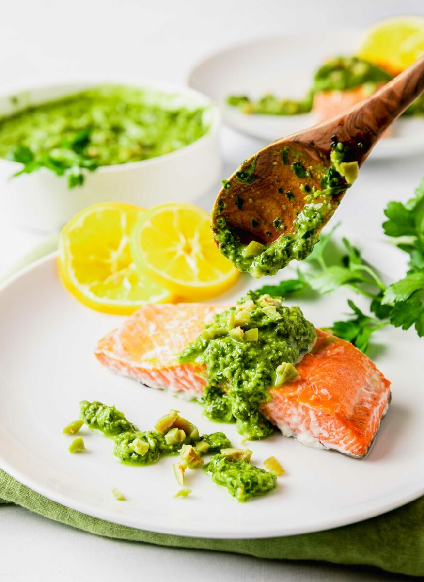 A wooden spoon is placing gremolata onto a salmon fillet.