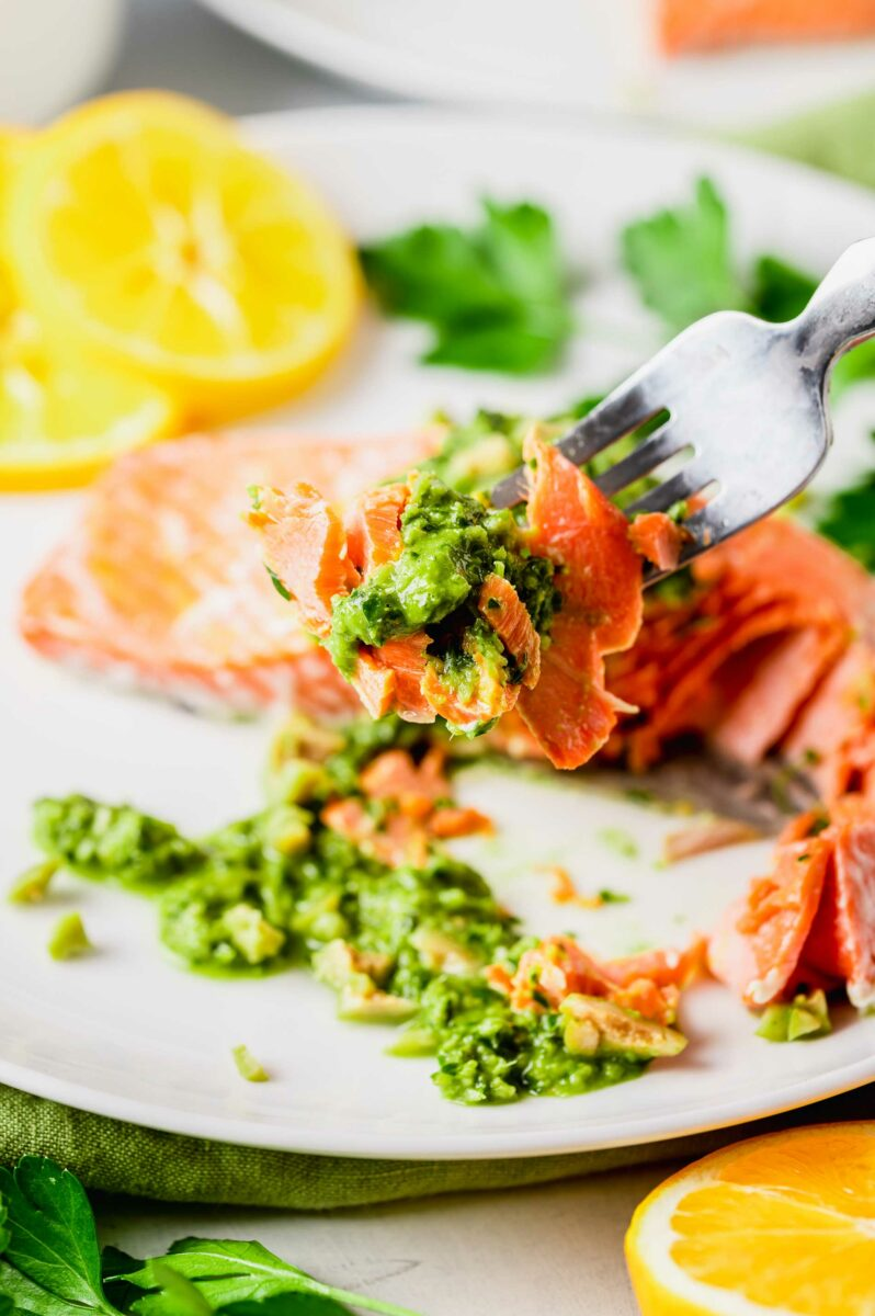 A fork is lifting a bite of salmon and garnish from the plate.
