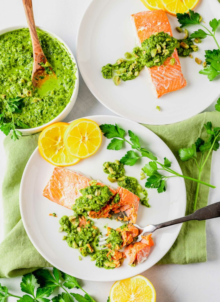 Two white plates have servings of garnished salmon.