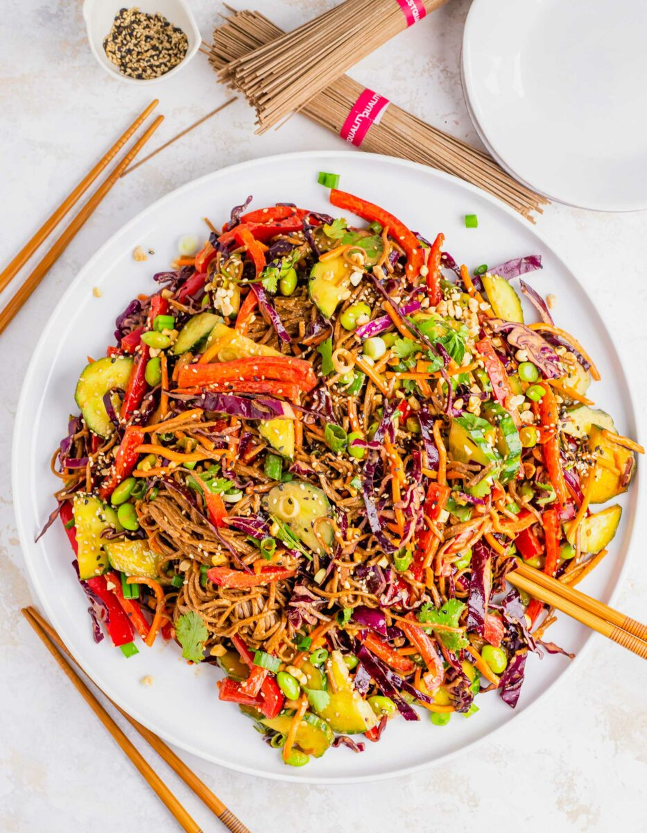 A large plate os soba noodle salad is garnished with sesame seeds.