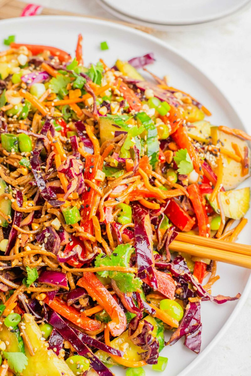 Chopsticks are placed on a white plate topped with soba noodle salad.