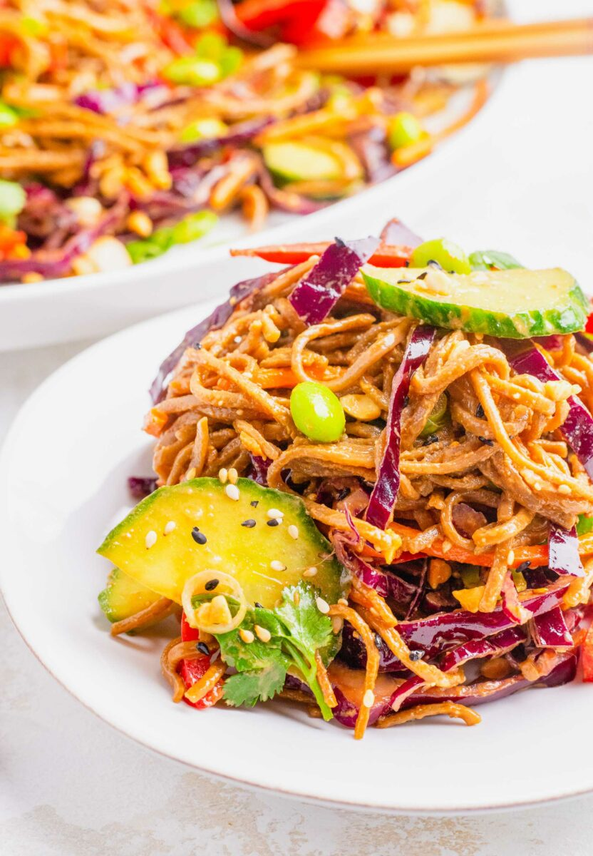 Vegetables and noodles are tossed and placed on a white plate.