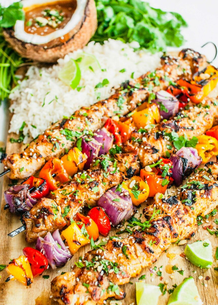 Chicken skewers are lined up with vegetable skewers.